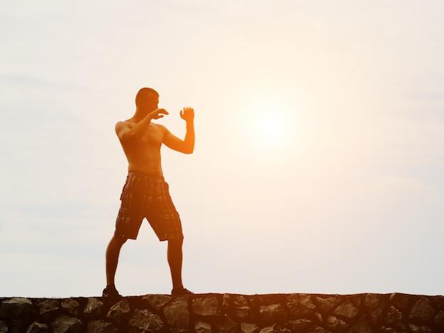 Молодой человек практикующих бокс на открытом воздухе