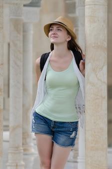 大理石の柱に囲まれた帽子とショートパンツの女の子