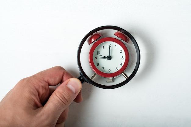 白い背景の上の男性の手で虫眼鏡の下の目覚まし時計。時間検索の概念