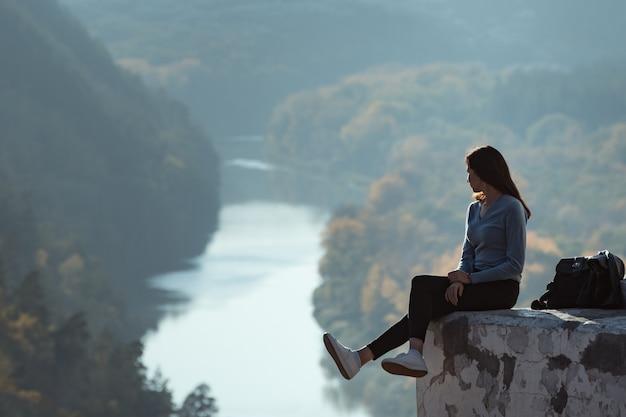 Девушка сидит на холме и смотрит вдаль на лес и реку.