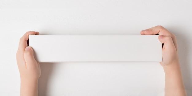 子供の手の中の白い長方形の段ボール箱。トップビュー、白い背景