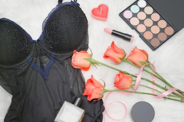 Черное тело, оранжевые розы, помада, духи и тени для век. модная концепция