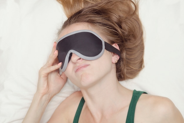 睡眠のためのマスクの若い女性は目を覚ますしたくないです。
