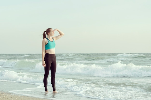 Девушка в спортивной одежде на пляже, глядя вдаль.