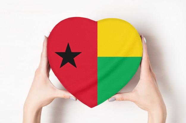 女性の手でハート形ボックスにギニアビサウの旗。白色の背景