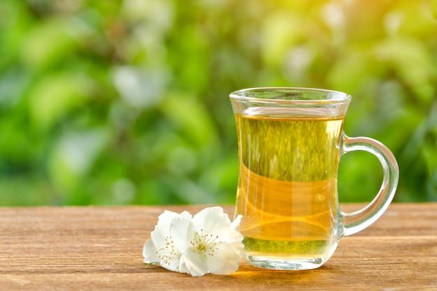 Прозрачная кружка чая с жасмином на фоне зелени, солнечного света. крупный план