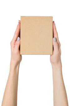 Маленькая картонная коробка в женских руках. вид сверху. изолировать