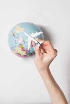 女性の手、地球の旅客機。フライトコンセプト