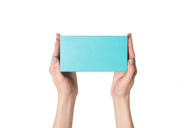 Прямоугольная бирюзовая коробка в женских руках. вид сверху. изолировать