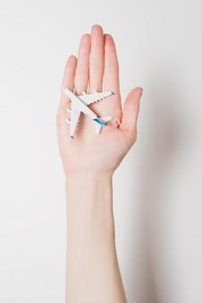 女性の手のひらに旅客機。安全なフライトの概念