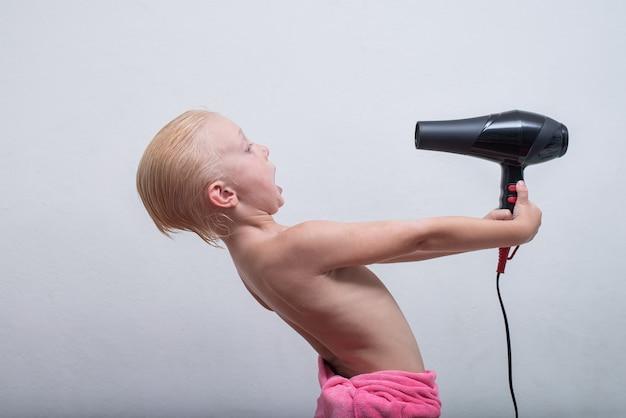 Белокурый мальчик с мокрыми волосами смешно сушится феном