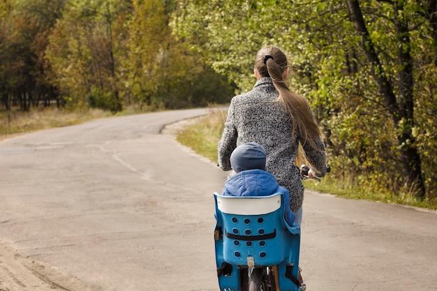 Мама и сын едут на велосипеде по осенней дороге. вид сзади.