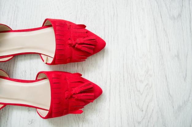 Красные открытые туфли на светлом деревянном столе. вид сверху