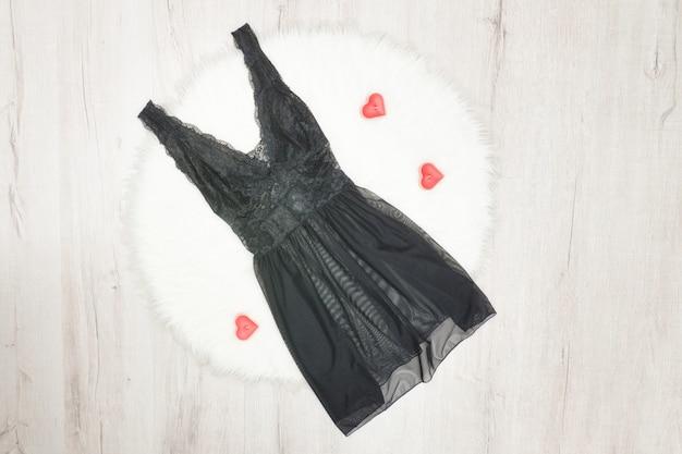 ファッションのコンセプト。白い毛皮の黒いレースのネグリジェ。赤いハート形のキャンドル