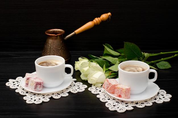 Пара чашек кофе с молоком, турка, восточные сладости, букет белых роз