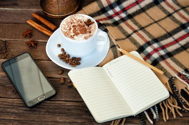 居心地の良い休暇。ラテマグカップ、ノートブック、鉛筆、電話、格子縞、コーヒー豆。上からの眺め
