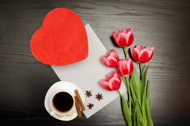 Красная коробка в форме сердца, розовые тюльпаны, белый лист и кружка кофе. черный стол. вид сверху