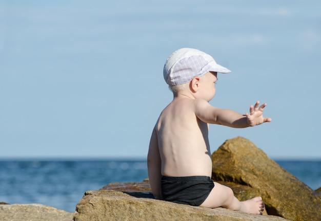 気にしないジェスチャー。スイミングトランクスの少年は海岸、テキストのための場所に座っています。