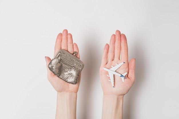 旅客機と女性の手のひらに財布。格安航空