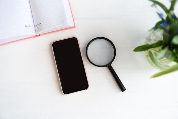 Смартфон с черным пустым экраном. блокнот, лупа и цветы на столе
