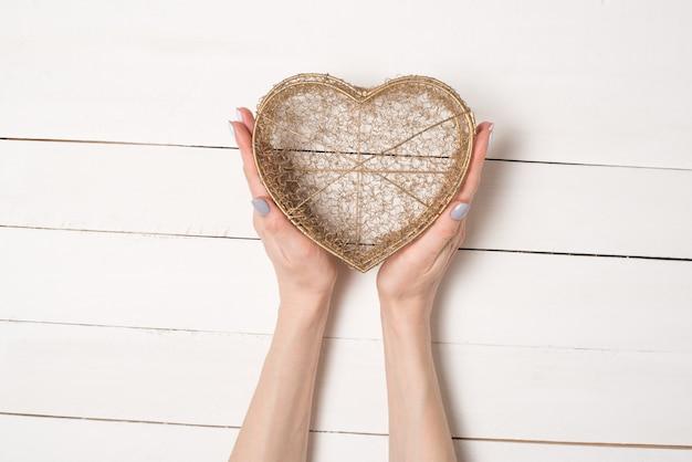 Женские руки держат металлическую проволоку прозрачную коробку в форме сердца на белом деревянном столе