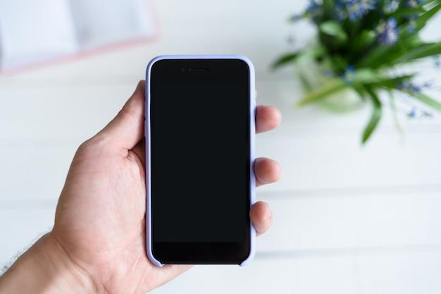 Мужская рука с смартфон. черный пустой экран. стол с блокнотом и цветами