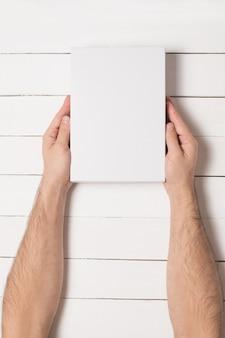 Белая прямоугольная коробка в мужских руках. вид сверху. белый стол