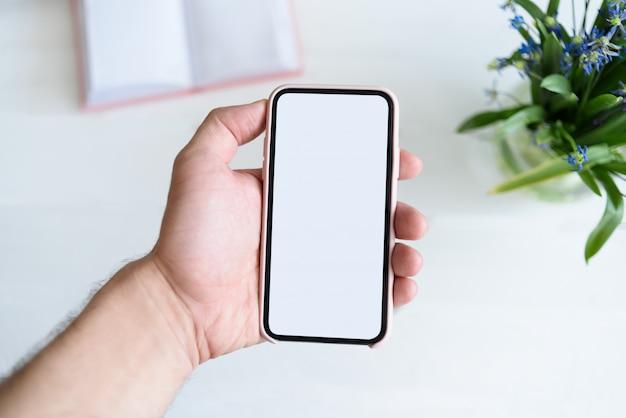Мужская рука с смартфон. белый пустой экран. стол с блокнотом и цветами