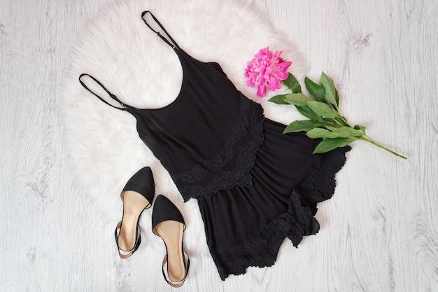 Черный комбинезон и туфли, пионы на белом меху. модная концепция