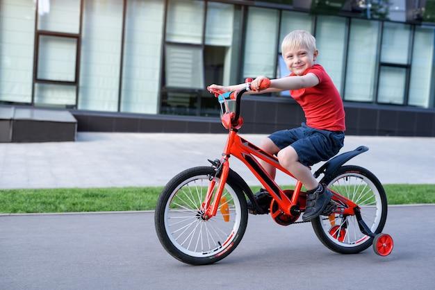 Белокурый мальчик едет на детском велосипеде