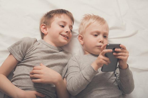 スマートフォンでベッドに横たわっている男の子