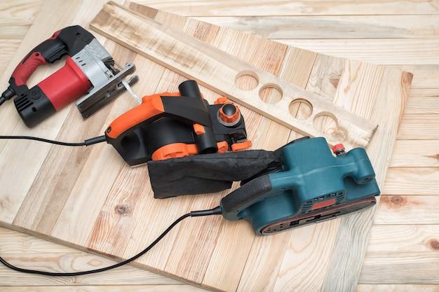 Набор ручных деревообрабатывающих электроинструментов для деревообработки и заготовки лежит на светлом деревянном фоне.