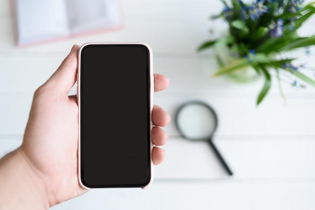 Мужская рука с смартфон. черный пустой экран. стол с блокнотом и цветами на фоне