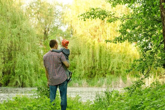 森の湖の近くに小さな息子とお父さんが立っています。