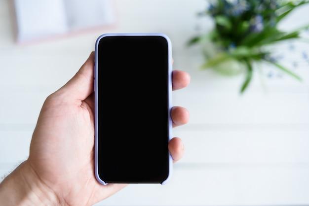 Мужская рука с смартфон. черный пустой экран. стол с блокнотом и цветами на