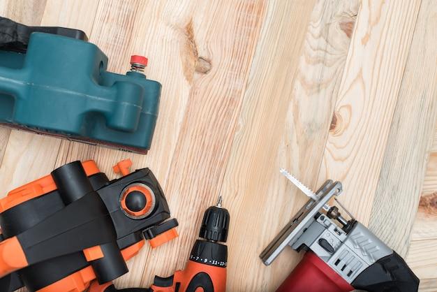 Набор ручных деревообрабатывающих электроинструментов для деревообработки на светлых деревянных. закрыть