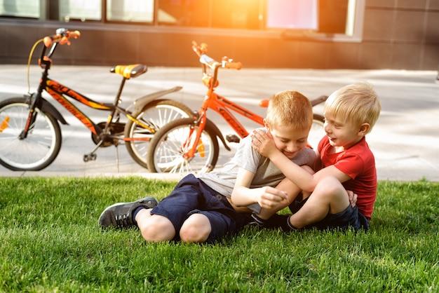 二人の少年が草の上に座って遊ぶ。サイクリング後の休憩、自転車