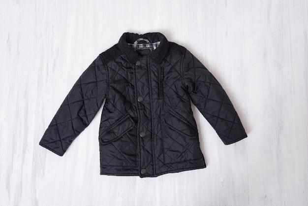 木製の背景に黒の子供キルティングジャケット。