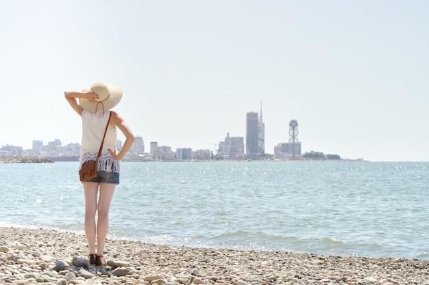 Девушка в шляпе, стоя на берегу моря. город на расстоянии. вид со спины