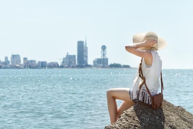 Девушка в шляпе, сидя на скале у моря. город на расстоянии. солнечный день