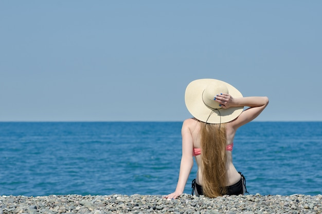 帽子と水着の美しい少女は、ビーチに座っています。海の上の空。後ろからの眺め