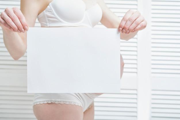 妊娠中の女性は白い空白のプラカードを保持しています。背中の腹