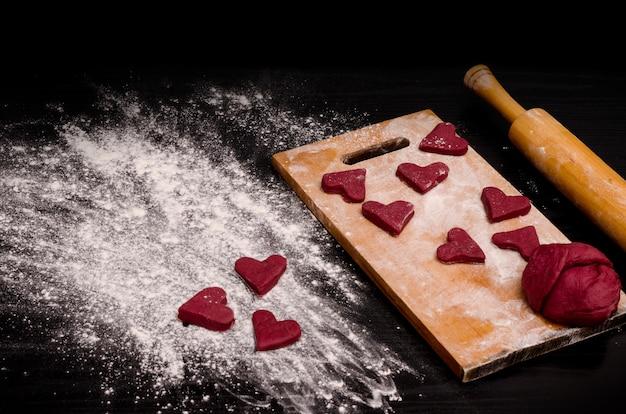 Красное сердечное печенье и кусок теста на деревянной доске
