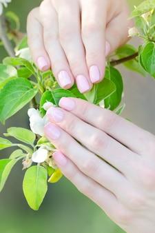 リンゴの木の花、マニキュアと女性の手。閉じる