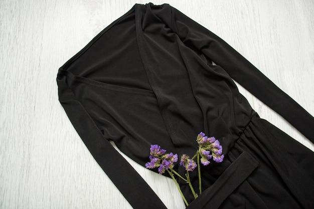 袖と野生の花の黒いドレス。おしゃれな