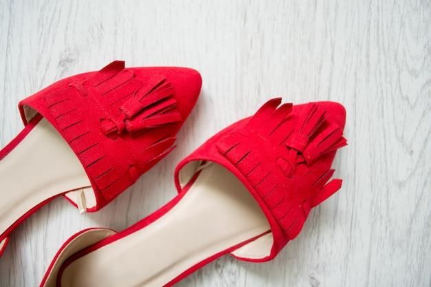 Красные открытые туфли на светлом деревянном. вид сверху
