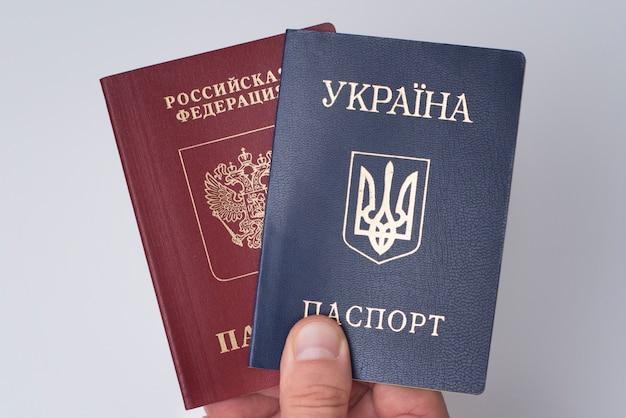 Украинские и российские загранпаспорта в мужской руке. белый закрыть