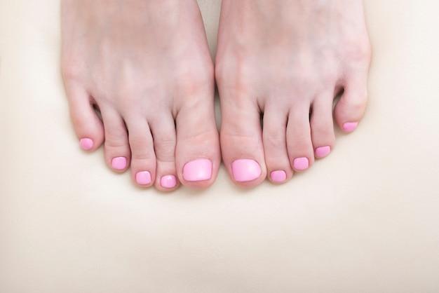 Женские пальцы ног крупным планом. розовый педикюр. белый