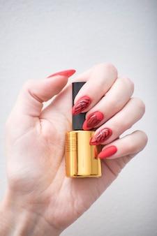 Красный маникюр с рисунком. флакон с лаком для ногтей