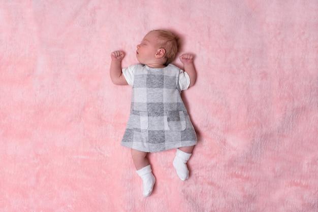 Спящая новорожденная девушка в платье на розовом одеяле. вид сверху. пространство для текста
